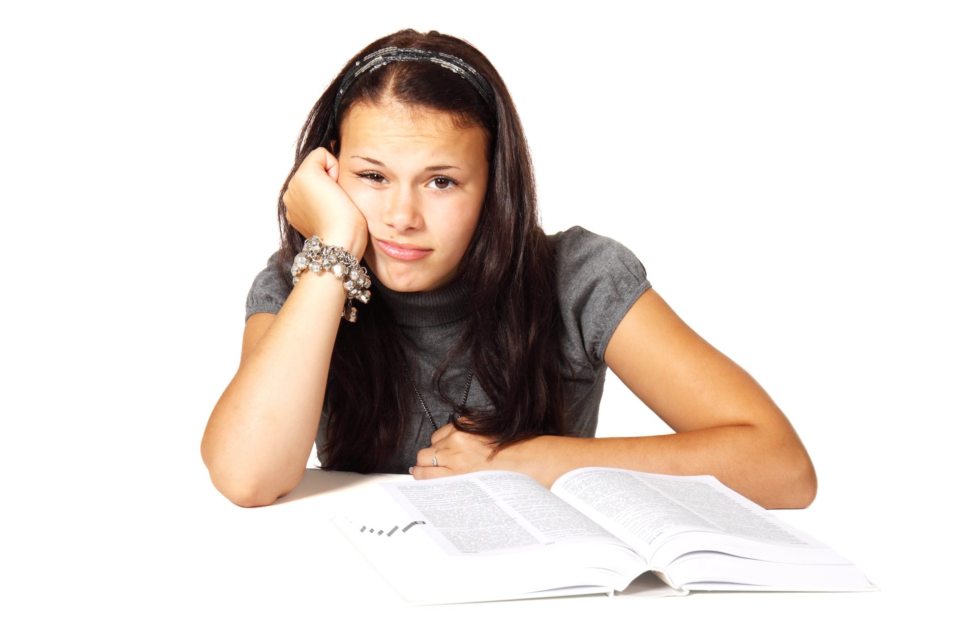 woman in black t shirt leaning on white table in front of white book